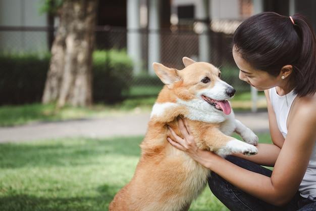 Aziatische vrouw met de welse hond van corgi pembroke