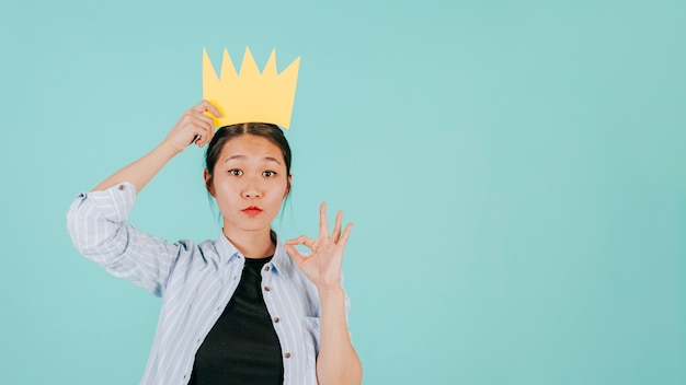 Aziatische vrouw met document kroon die ok gesturing