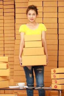 Aziatische vrouw met dozen voor haar werk thuis online winkelbedrijf