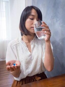 Aziatische vrouw met een glas water en pillen
