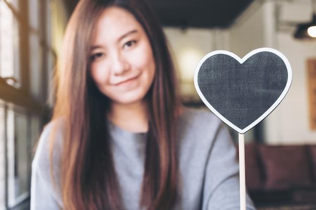 Aziatische vrouw met een lege hart vorm schoolbord teken met gevoel blij en verliefd