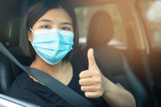 Aziatische vrouw met een masker in een auto masker om coronavirus te voorkomen, chauffeurs in de straten van de stad tijdens de uitbraak van covid-19