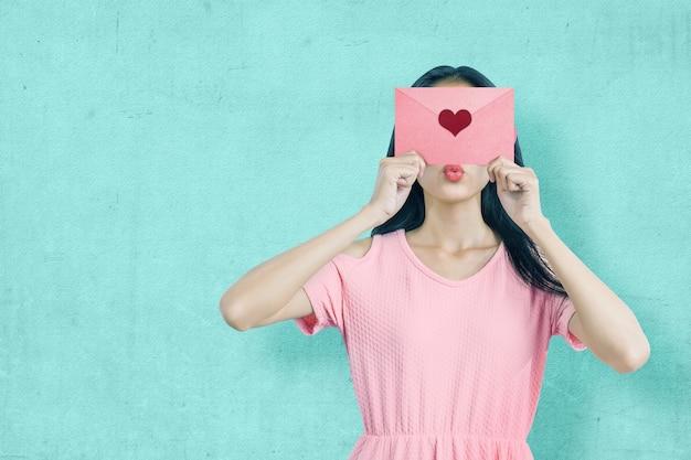 Aziatische vrouw met een roze envelop met hart met een blauwe muur achtergrond. valentijnsdag