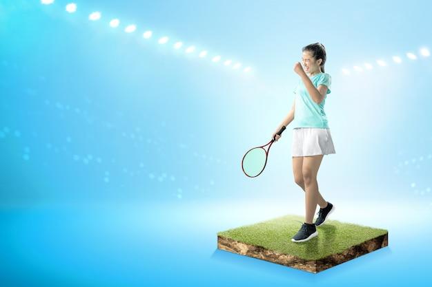 Aziatische vrouw met een tennisracket in haar handen en opgewekte uitdrukking