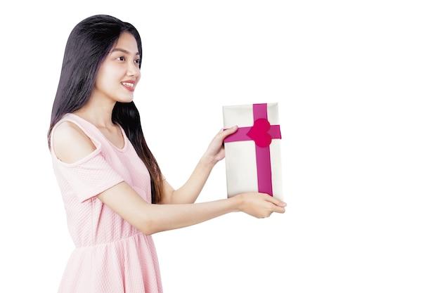 Aziatische vrouw met een witte geschenkdoos met een rood lint en hartvorm geïsoleerd op witte achtergrond