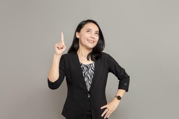 Aziatische vrouw met een zwart pak die omhoog kijkt en omhoog wijst met een hand die lacht