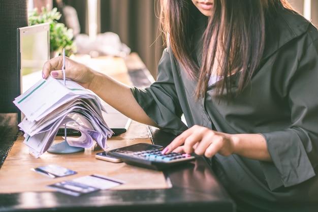Aziatische vrouw met financiële rekeningen die schuld berekenen