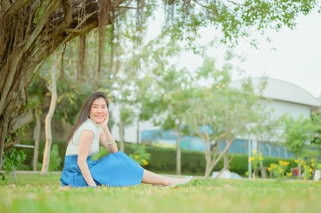 Aziatische vrouw met gelukkige uitdrukking ontspannende zitting op gras in park, de zomer zonnige dag. buitenshuis. natuur.