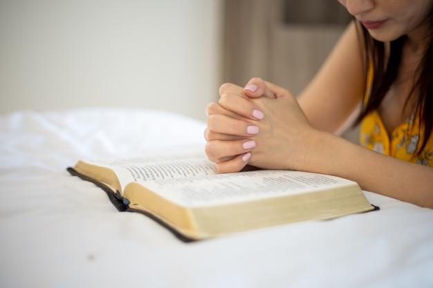 Aziatische vrouw met hand bidden, handen gevouwen in gebed op het bed. concept voor geloof, spiritualiteit en religie.