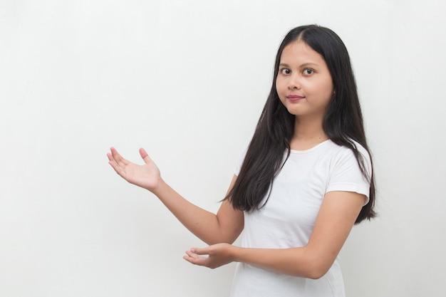 Aziatische vrouw met handpunt op lege ruimte