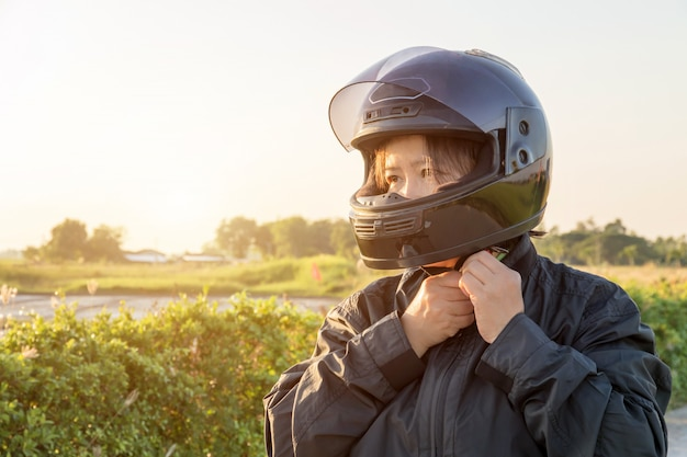 Aziatische vrouw met helm en dragen en vastmaken alvorens grote fietsmotorfiets op de weg voor veiligheid te berijden