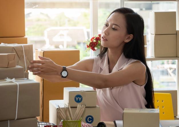Aziatische vrouw met het opstarten van de kleine ondernemer freelance ondernemer thuis het werken. het controleren van de productbestelling.