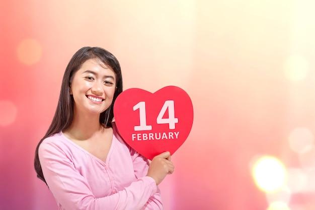 Aziatische vrouw met het rode hart met 14 februari-bord met een gekleurde muur. valentijnsdag