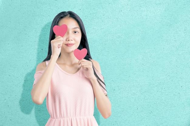 Aziatische vrouw met het rode hart met een gekleurde achtergrond. valentijnsdag
