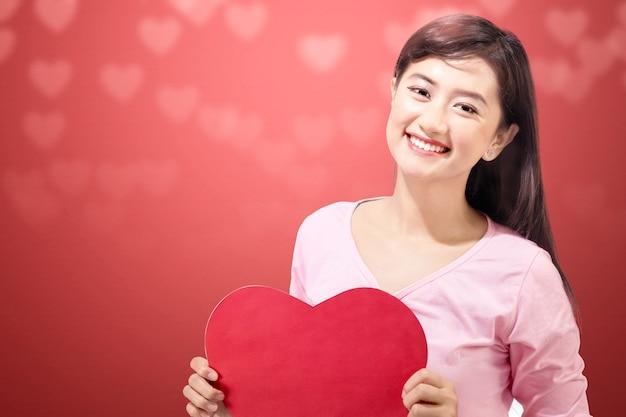 Aziatische vrouw met het rode hart met een gekleurde muur. valentijnsdag