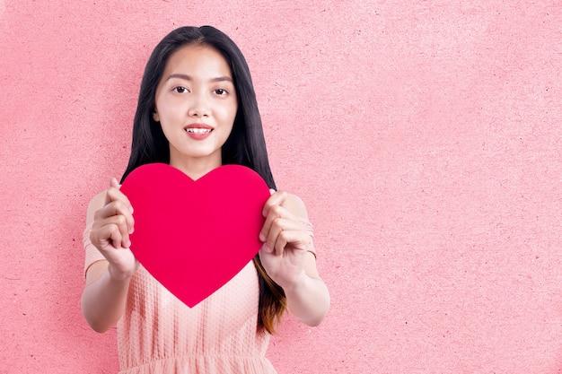 Aziatische vrouw met het rode hart met een roze muur achtergrond. valentijnsdag