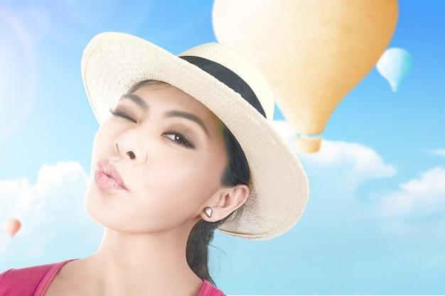 Aziatische vrouw met hoed die een selfie neemt met kleurrijke luchtballon die met blauwe hemelachtergrond vliegt