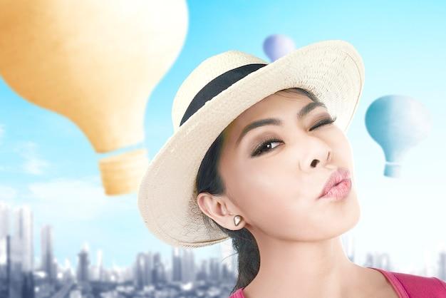Aziatische vrouw met hoed die een selfie neemt met kleurrijke luchtballon die met stadsachtergrond vliegt