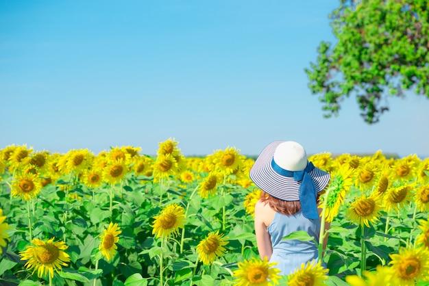 Aziatische vrouw met hoed op een gebied van bloemen, die op zonnebloemgebied genieten van
