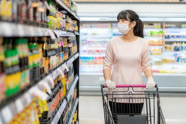 Aziatische vrouw met hygiënisch masker en rubberen handschoen met winkelwagentje in kruidenier en op zoek naar saus of smaakstof om te kopen tijdens covid-19-uitbraak ter voorbereiding op een pandemische quarantaine