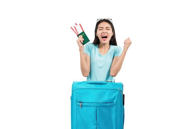 Aziatische vrouw met kaartje en paspoort dat op koffer leunt