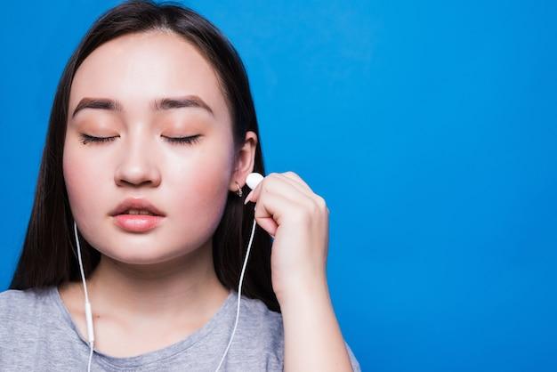 Aziatische vrouw met koptelefoon en luisteren naar muziek
