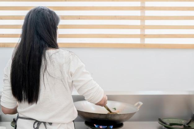 Aziatische vrouw met lang zwart haar kookt voedsel in stalen pan op fornuis met kopieerruimte erachter.
