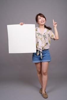 Aziatische vrouw met leeg wit bord met copyspace