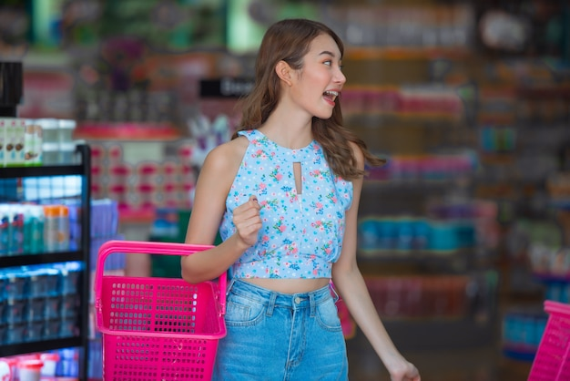 Aziatische vrouw met mand het winkelen ding in schoonheidswinkel.