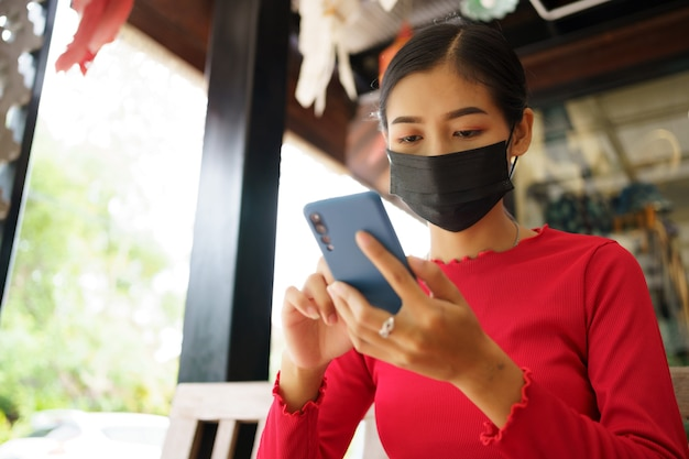 Aziatische vrouw met masker met behulp van mobiel