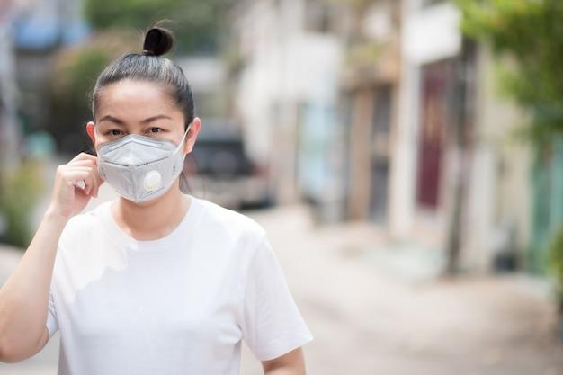 Aziatische vrouw met masker ter voorkoming van pm 2.5-stof en coronavirus, covid 19