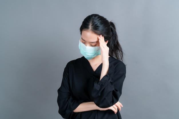Aziatische vrouw met medisch gezichtsmasker beschermt filterstof pm2.5 anti-vervuiling, anti-smog en covid-19 en heeft hoofdpijn op een grijze achtergrond