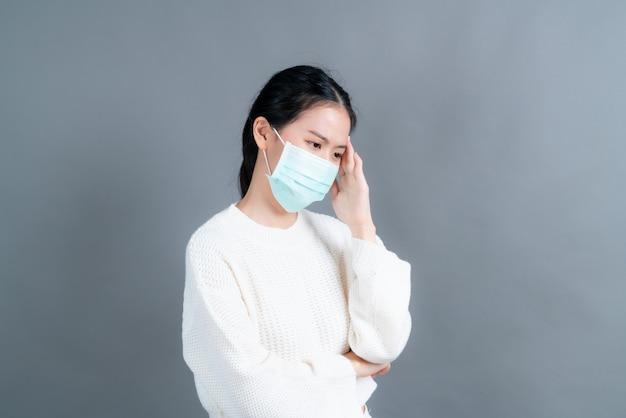 Aziatische vrouw met medisch gezichtsmasker beschermt filterstof pm2.5 anti-vervuiling, anti-smog en covid-19 en heeft hoofdpijn op grijze muur