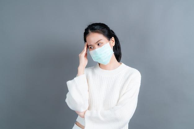 Aziatische vrouw met medisch gezichtsmasker beschermt filterstof pm2.5 anti-vervuiling, anti-smog en covid-19 en heeft hoofdpijn