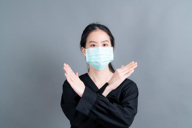 Aziatische vrouw met medisch gezichtsmasker beschermt filterstof pm2.5 anti-vervuiling, anti-smog en covid-19 op grijze muur