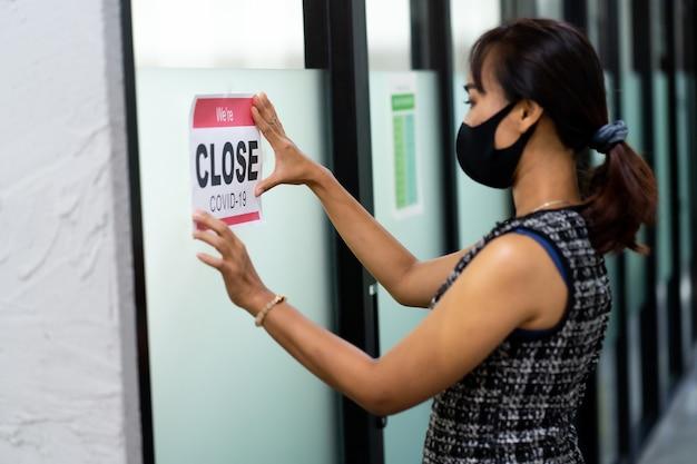 Aziatische vrouw met medisch masker zet een tijdelijke gesloten wegens covid-19 pandemie teken banner op deur en ramen op kantoor