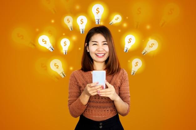 Aziatische vrouw met mobiele telefoon met gloeilamp pictogram en dollarteken