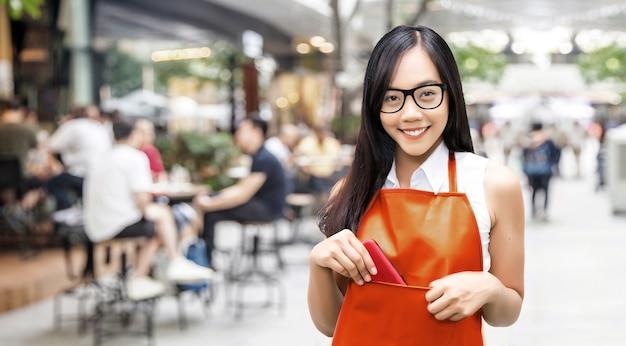 Aziatische vrouw met oranje schort en glazen met vage caféachtergrond