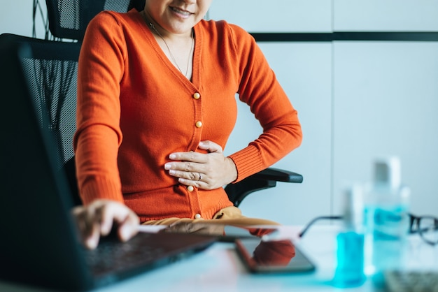 Aziatische vrouw met pijnlijke buikpijn tijdens het werken vanuit huis