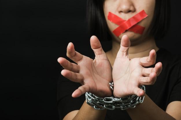 Aziatische vrouw met plakband over mond en kettingen aan polsen