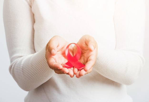 Aziatische vrouw met roze de voorlichtingslint van borstkanker op handenbehandeling liefdadigheid