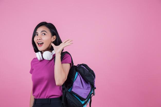 Aziatische vrouw met rugzak en hoofdtelefoon op studio roze achtergrond.