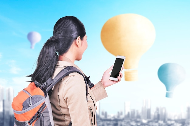 Aziatische vrouw met rugzak en smartphone kijken naar kleurrijke luchtballon vliegen met stadsgezicht achtergrond