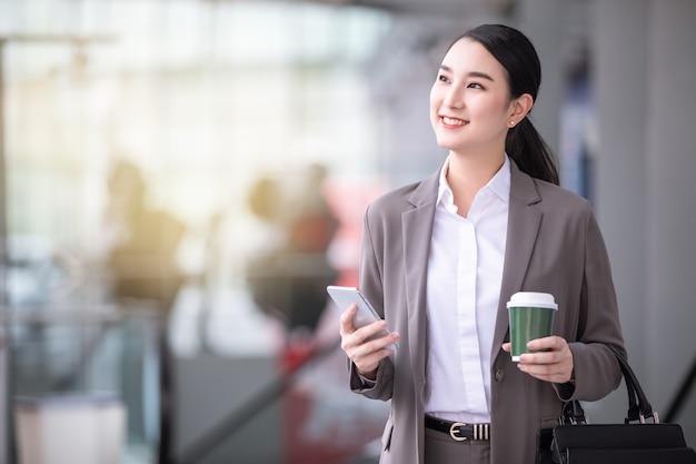 Aziatische vrouw met smartphone die zich tegen straat vaag gebouw bevindt. mode zakelijke foto van mooi meisje in casual suite met telefoon en kopje koffie