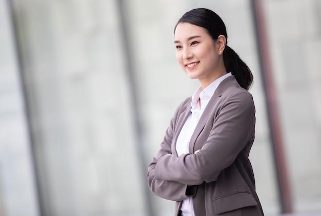 Aziatische vrouw met smartphone die zich tegen straat vaag gebouw bevindt. mode zakelijke foto van mooi meisje in casual suite.