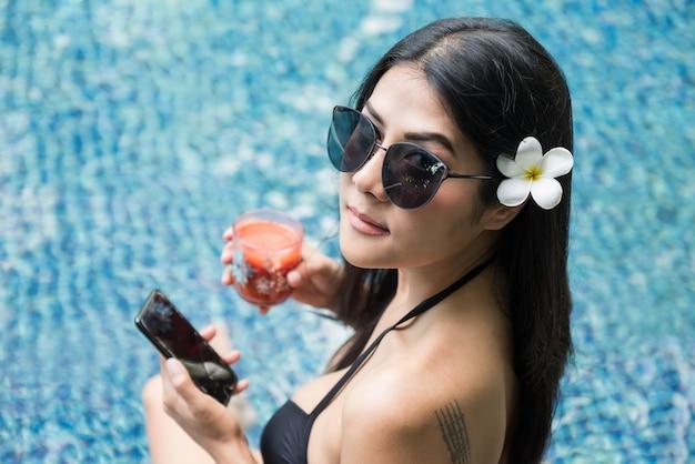 Aziatische vrouw met tatoeage ontspannen bij zwembad