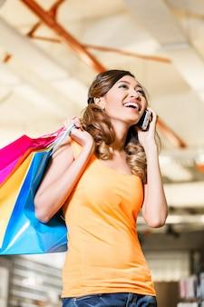 Aziatische vrouw met telefoon winkelen mode