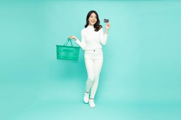 Aziatische vrouw met winkelmandje en creditcard tonen op lichtgroene achtergrond