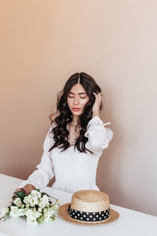 Aziatische vrouw met witte bloemen wat betreft krullend haar. studio shot van vrolijke japanse dame zittend aan tafel met eustoma boeket.