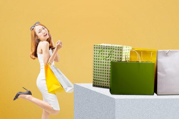 Aziatische vrouw met zonnebril met boodschappentassen staan